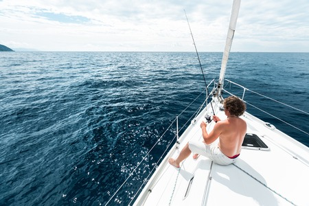 warm water fish: Man fishing in the sea from the boat