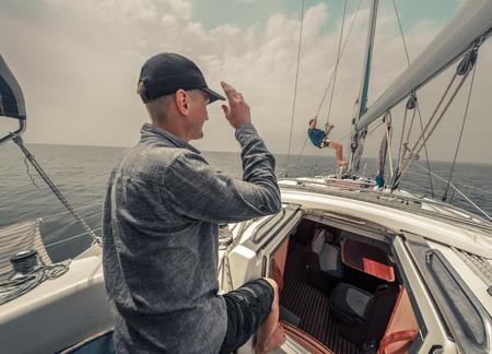 voilier ancien: Deux jeunes marins adultes sur le bateau à voile dans une mer