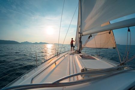 Jeune homme sur le bateau à voile au coucher du soleil