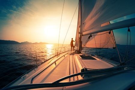 Young man on the sailing boat at sunset Banque d'images
