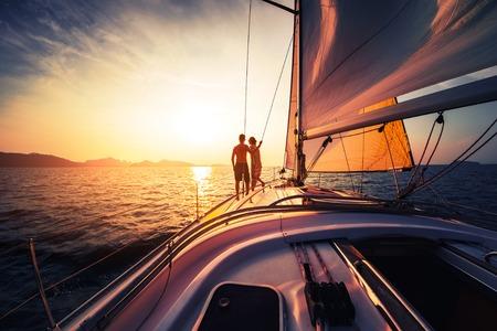 Couple sur le bateau à voile au coucher du soleil Banque d'images
