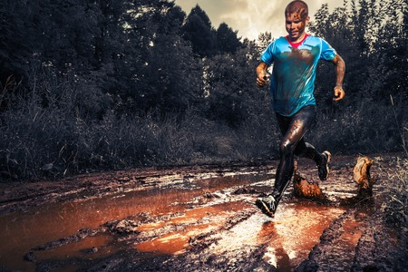 Man athlete running in the forests trail and crossing dirty puddle