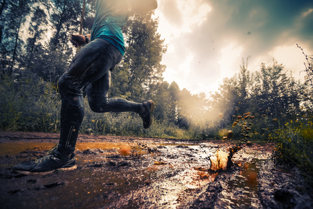cropped out: Trail running athlete crossing the dirty puddle in the forest