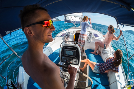 sailing crew: Crew of young friends sailing in a blue sea on the yacht