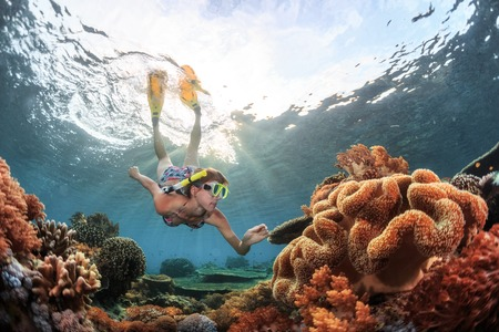 Young woman snorkeling over coral reef in the tropical sea. Bali island