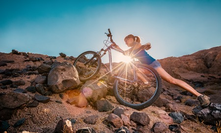 Woman with bicycle crossing rocky terrain in the desert at sunny day 스톡 콘텐츠
