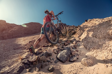 Man with bicycle crossing rocky terrain in the desert at sunny day
