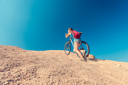 off road biking: Young lady climbing up the sandy hill with a bicycle in the desert at sunny day