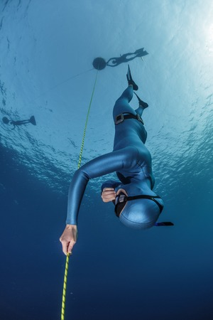Lady freediver descending along the rope. Free immersion discipline