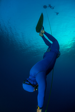 free diver: Free diver falling into deep darkness along the rope with monofin