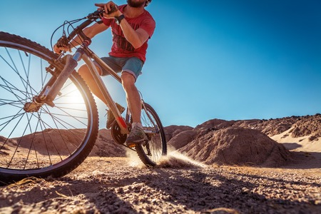 off road biking: Man cycling in the desert with lot of dust