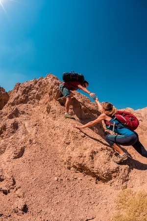 help: Two hikers crossing rocky terrain in the desert at sunny day