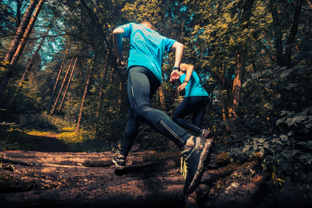 Two athlete running through the forest crossing wood barrier