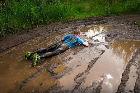 농촌 도로에서 더러운 웅덩이에 떨어지는 선수