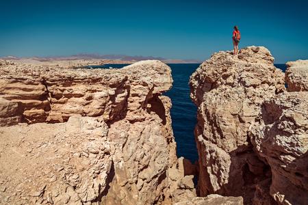monte sinai: Señora joven que se coloca en la parte superior del acantilado en el Parque Nacional de Ras Mohamed, Egipto Foto de archivo