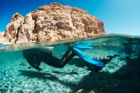 ras: Split shot with diver underwater and rocky land of the Ras Muhammad National Park, Red Sea, Egypt