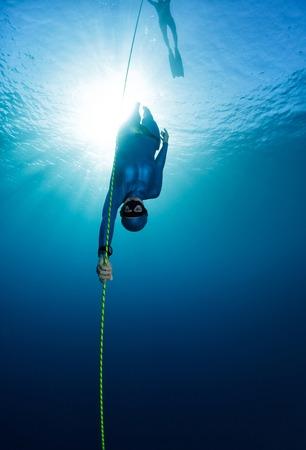 無料のダイバーがロープに沿って降順