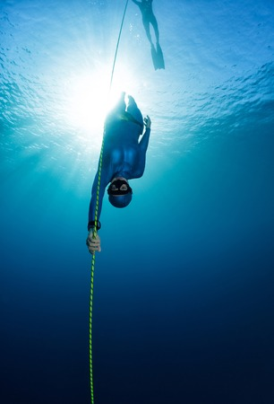 Free diver descending along the rope Stock Photo