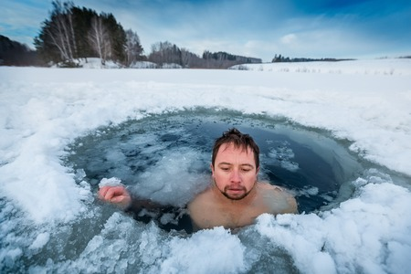 Young man swimming in the winter lake in the ice hole Stockfoto