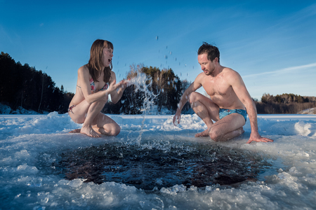 Young couple having fun and splahing the water of a winter lake