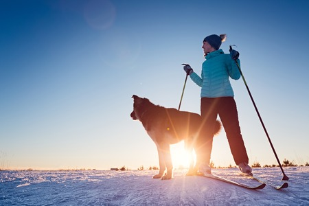 Woman skiing in a winter field with the dog