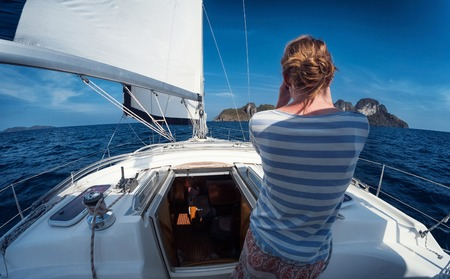 Lady sailor standing on the yacht and watching to the binoculars at sunny day Stock Photo