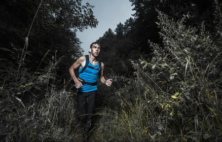 outdoor sport: Trail running athlete moving through dark forest Stock Photo