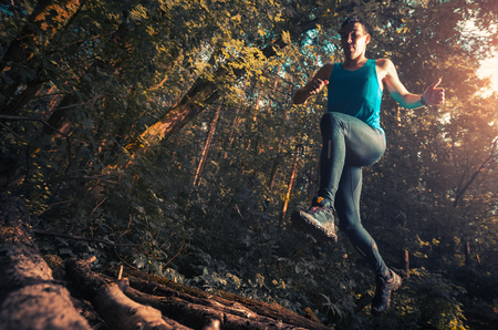 Trail running athlete jumping over wood barrier in the forest Imagens