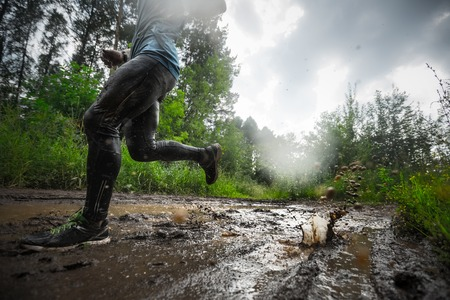 Trail running athlete moving through the dirty puddle in the rural road