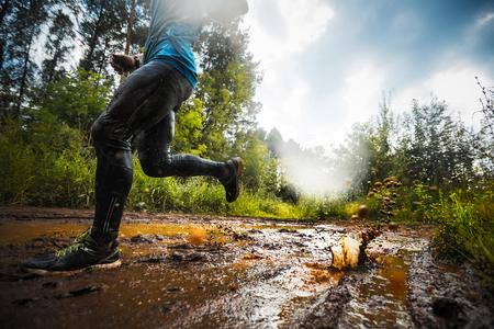 Trial course athlète se déplaçant à travers la flaque d'eau sale dans la route rurale
