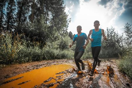 Dos carreras de montaña atleta en movimiento a través del charco sucio en el camino rural