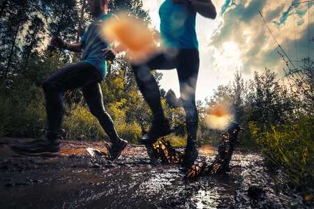 Two trail running athlete moving through the dirty puddle in the rural road