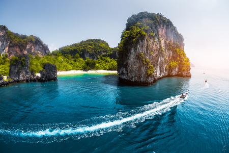 Vue aérienne de la mer, avec des bateaux thai longtail traditionnels et l'éperon rocheux sur le fond