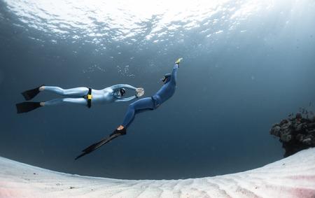 Deux apnéistes Finning sur le fond de la mer de sable