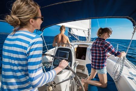 voilier ancien: Jeunes amis qui naviguent dans une mer bleue sur le yacht Banque d'images