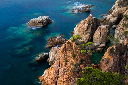 water town: Sea with rocks and transparent water at sunrise, Town of Tossa de Mar, Spain Stock Photo