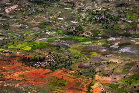 Traditional Malagasy village among red soils and green fields. Madagascar