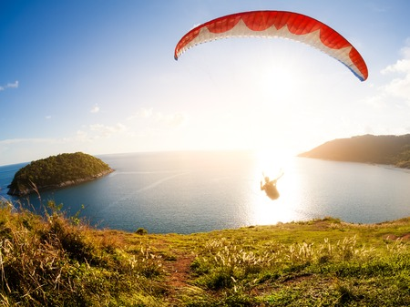 parachuting: Paraglider flying over the water Stock Photo