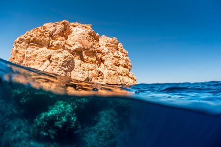 Split shot with coral reef underwater and rocky land of the Ras Muhammad National Park, Red Sea, Egypt Stock Photo
