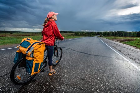 loaded: Lady hiker standing with loaded bicycle on the paved asphalt road with stormy clouds on the background