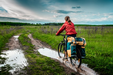 loaded: Young lady hiker with loaded bicycle riding through the puddle on a wet rural road
