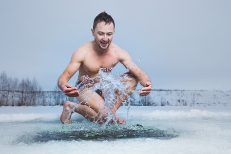 frozen lake: Young man having fun near the ice hole