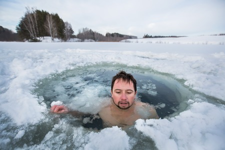 Young man swimming in the winter lake in the ice hole Stock Photo