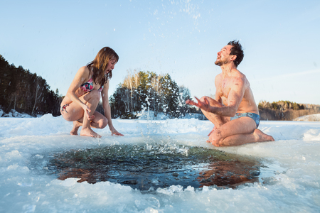 sunny cold days: Young couple having fun and splashing the water of a winter lake