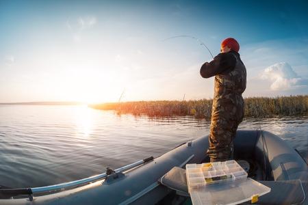 bateau de pêche: Homme de pêche du bateau sur le lac au coucher du soleil
