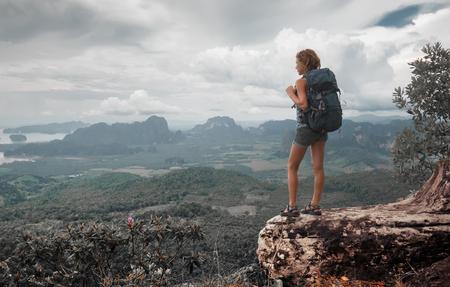 mujer mirando el horizonte: Excursionista Señora joven con mochila de pie en la cima de la montaña y disfrutar de vistas al valle Foto de archivo