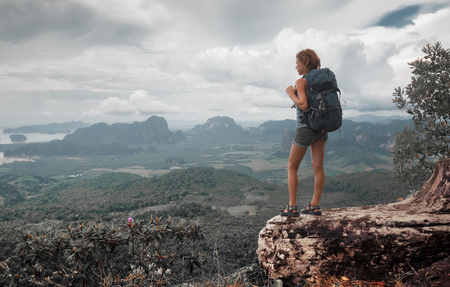 looking out: Young lady hiker with backpack standing on top of the mountain and enjoying valley view Stock Photo