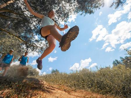 Berglopen atleet springen over camear op zonnige dag Stockfoto