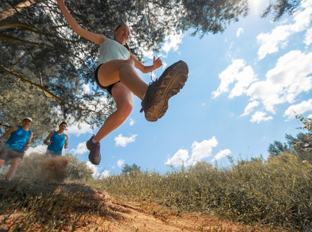 Trail running athlete jumping over camear at sunny day