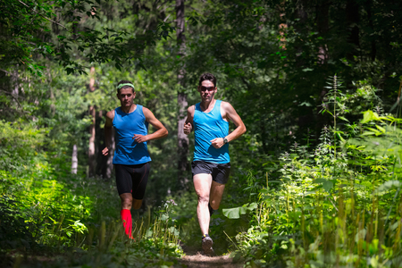 uniform green shoe: Trail running athletes moving through the forest